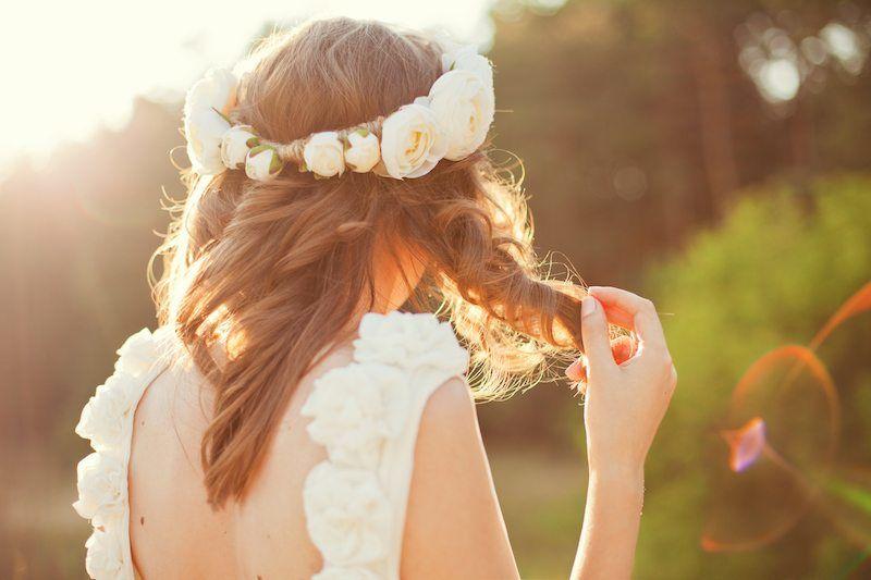 Braut mit Blumenkranz spielt mit ihren Haaren