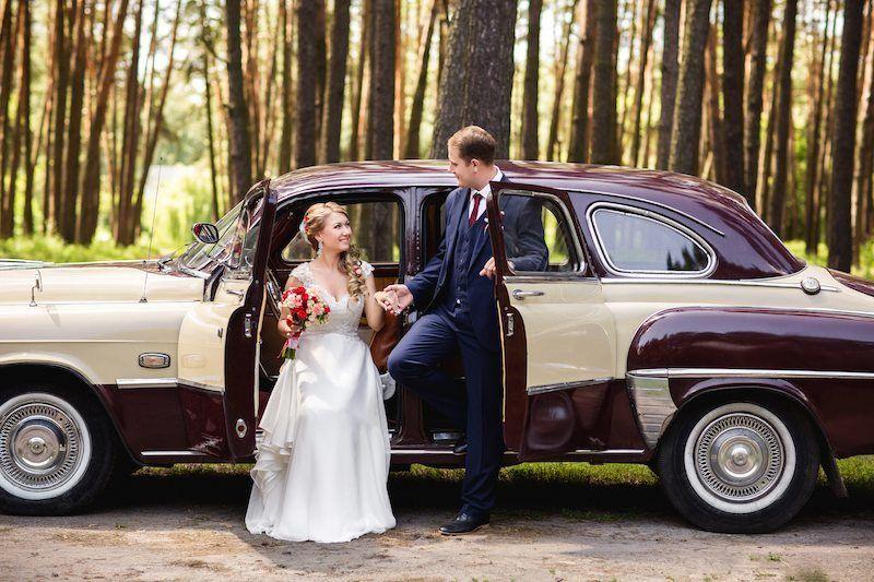 Brautpaar posiert vor einem Oldtimer
