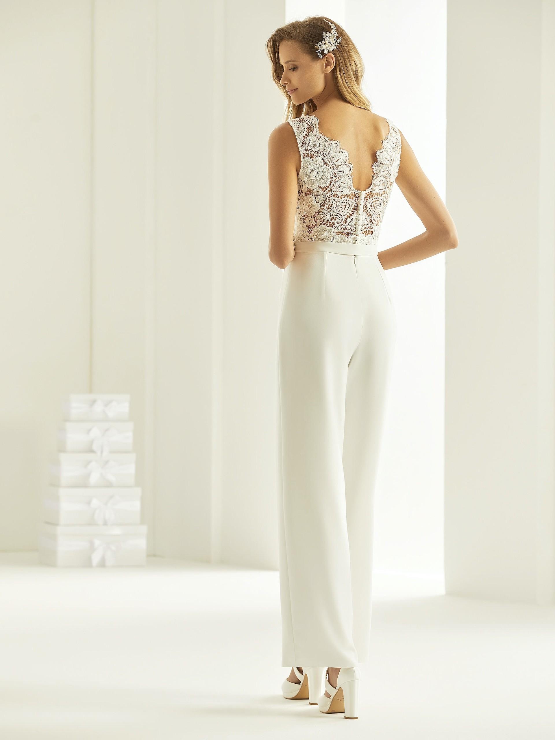 Braut-Jumpsuit mit weiter Hose, Spitzentop mit V-Ausschnitt und Gürtel von Bianco Evento, Modell Trinity
