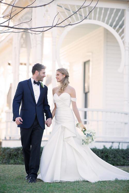 Cremefarbenes, schulterfreies Brautkleid mit Falten ud Drapierungen sowie Schleppe von Martina Liana