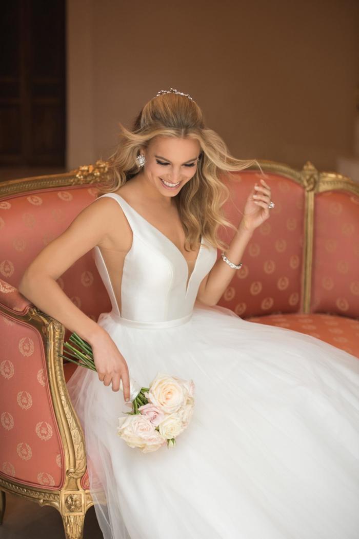 Weißes Brautkleid im Prinzessschnitt mit Tüllrock, tiefem V-Ausschnitt und seitlichen Cutouts von Stella York