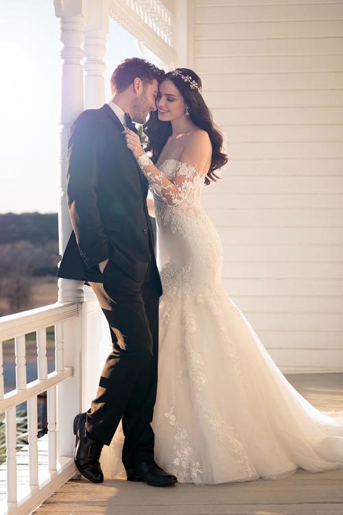 Weißes, schulterfreies Brautkleid im Fit-and-Flare-Schnitt mit Spitze und langen Spitzenärmeln von Martina Liana