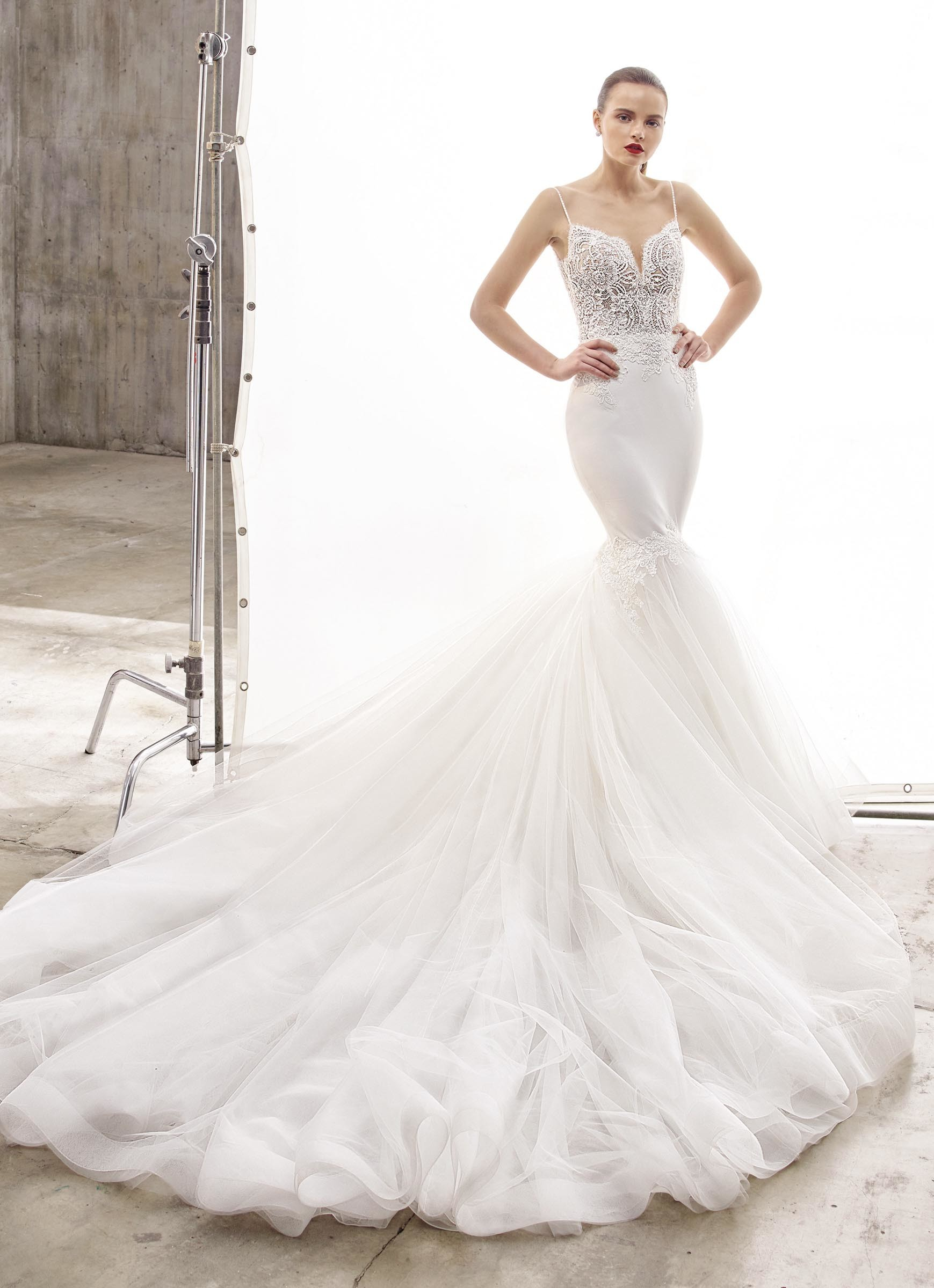 Weißes Brautkleid im Fit-and-Flare-Schnitt mit transparenter Spitzenkorsage, Spaghettiträgern und voluminöser Schleppe von Enzoani, Modell Naya, Frontansicht