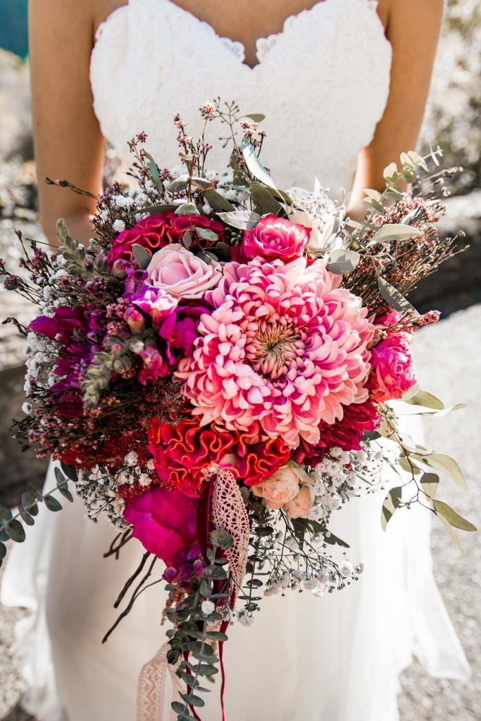 moderner Brautstrauß in lila mit Hahnenkamm und Schleierkraut