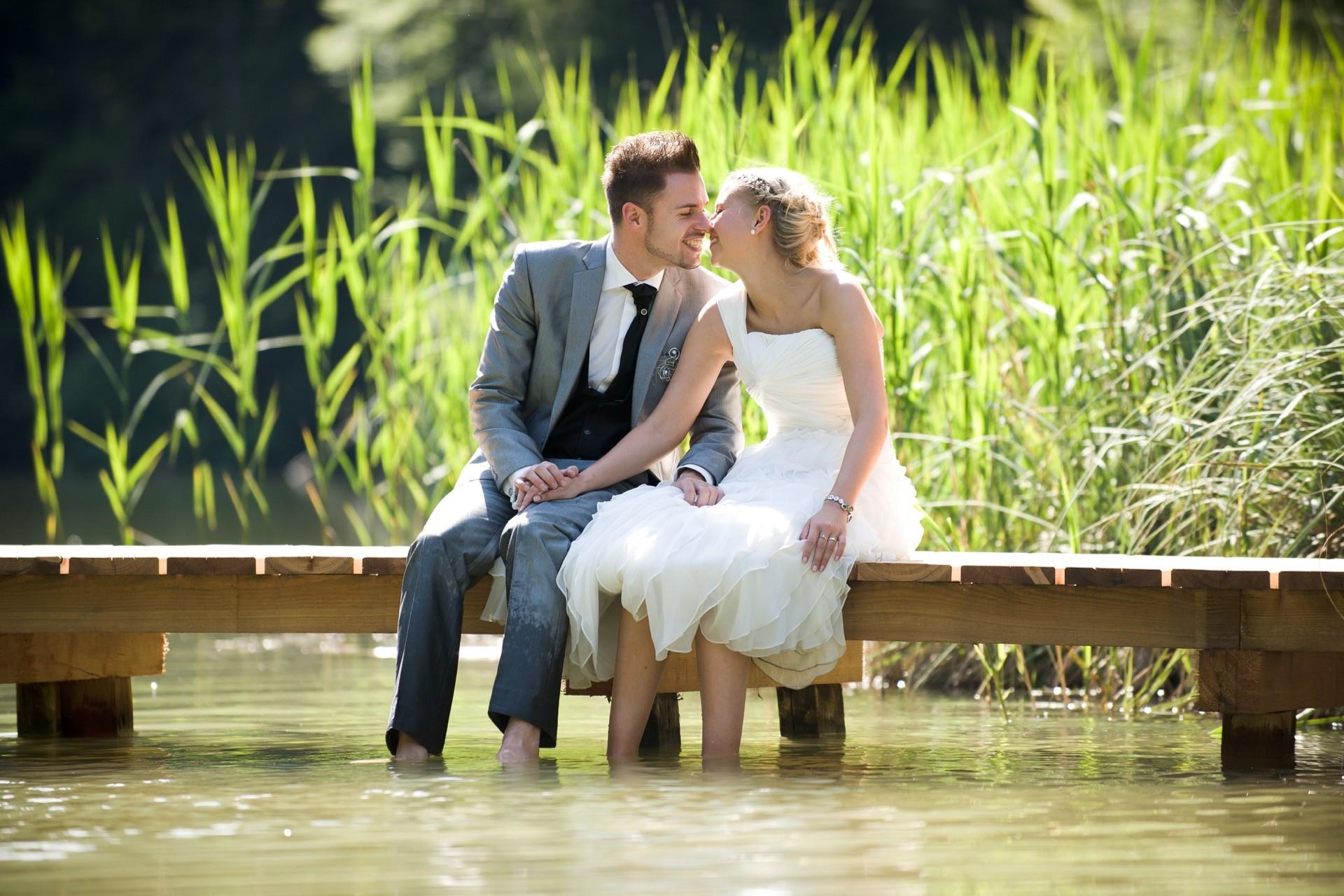 Braut und Bräutigam sitzen romantisch an einem See